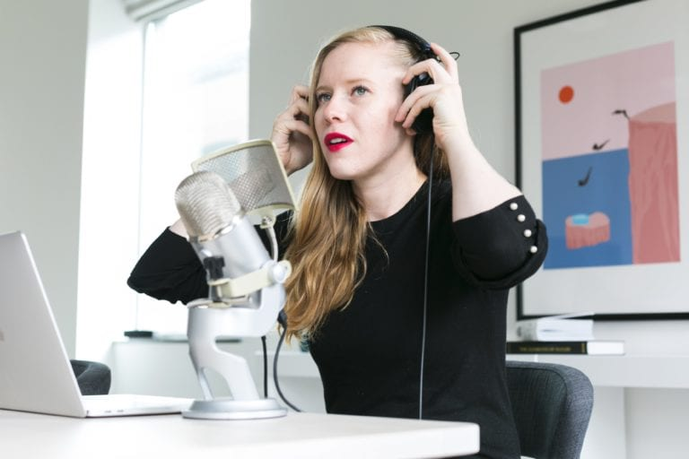 woman adjusting headphones at microphone