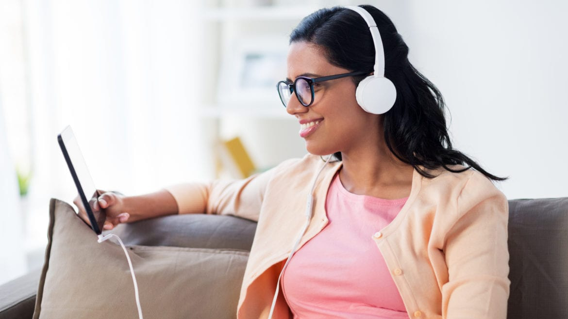 happy young woman sitting on sofa with tablet pc computer and headphones listening to podcasts at home