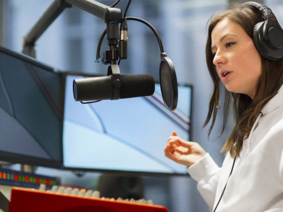 Young female host talking on microphone while wearing headphones in radio studio