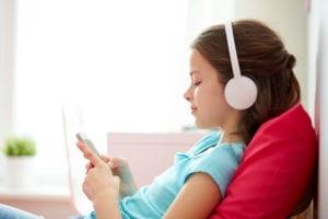 girl listening with headphones in her home