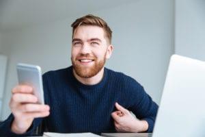 Smiling man holding smartphone