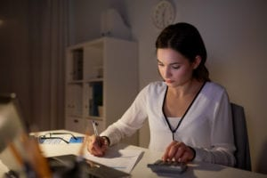 Woman working at desk in the evening with paper and calculator.