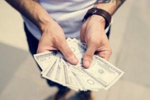 Standing gentleman shown from chest down with outstretched hands holding dollar bills