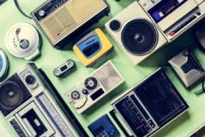Overhead view of multiple listening devices such as radios, Walkmans and cassette players.