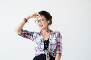 Attractive young woman in plaid colorful shirt, glasses and white earphones smiles while draping her hand on her forehead against white background.