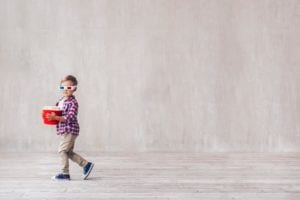 Little boy in 3D glasses walking away with a tub of popcorn in hand.
