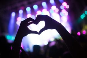 Hands in shadow with fingers creating a heart against a background of a lit concert stage.
