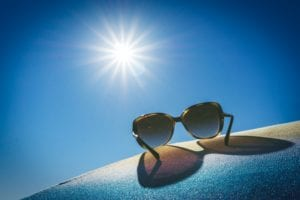 Bright summer sun against a very blue sky with a pair of sunglasses on a surface in the foreground.
