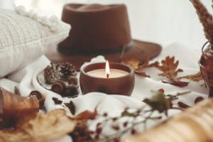 Beautiful fall leaves, candle light, hat, berries, nuts, acorns, cotton, cones, cinnamon on soft white background.