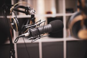 Broadcasting microphone with headset on stand agains blurred background of a studio.