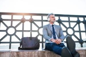 Handsome mature businessman sitting on a bridge, holding laptop and using headphones.