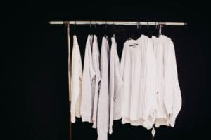 Single clothes wrack against a black background with various white shirts hanging on it.