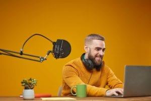 Studio shot of smiling young Caucasian man typing something on his laptop, mustard background