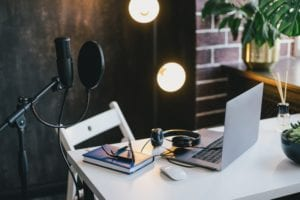 Items for recording podcast: professional microphone, earphones and laptop on white table in cozy home studio with black walls and lots of plants.